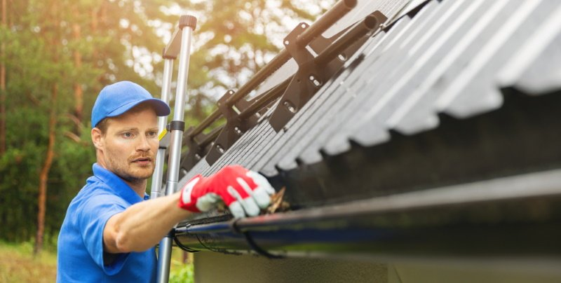 a technician cleaning a house gutter in Chicago
