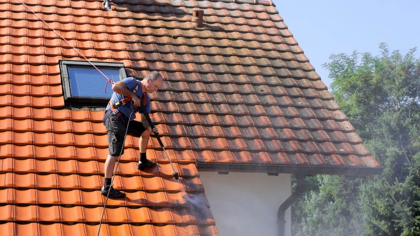 a person soft washing a roof