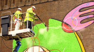 two technicians cleaning graffiti with a pressure washing machine