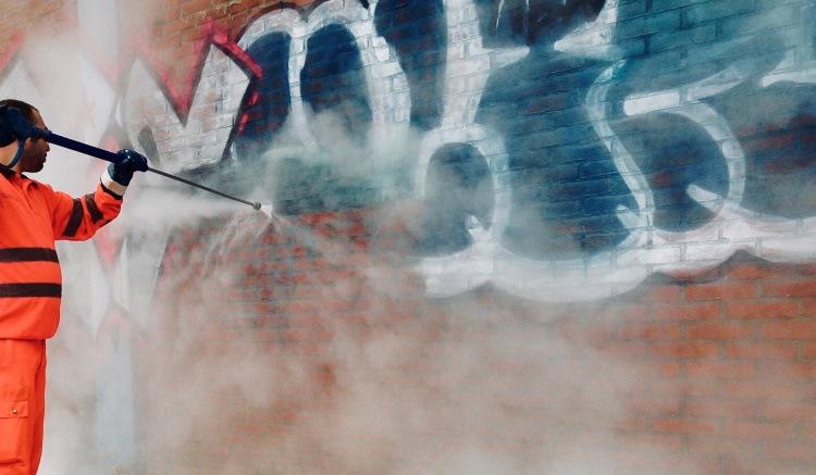 a technician using pressure washer spraying over graffiti