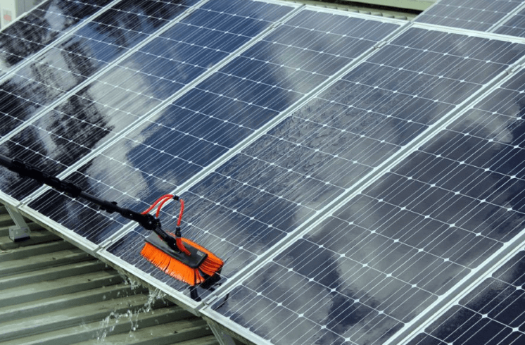 A technician that is cleaning a solar panels on a roof